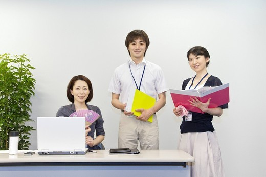 Stock Photo: 1436R-433756 Businessman and two businesswomen in business casual at office