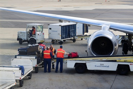 Stock Photo: 1436R-434200 Baggage handlers loading luggage onto a convey into an airplane on the tarmac of New Orleans Airport