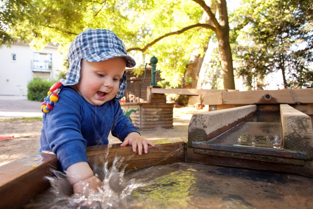 boy playing with water splashing, summer on playground : Stock Photo