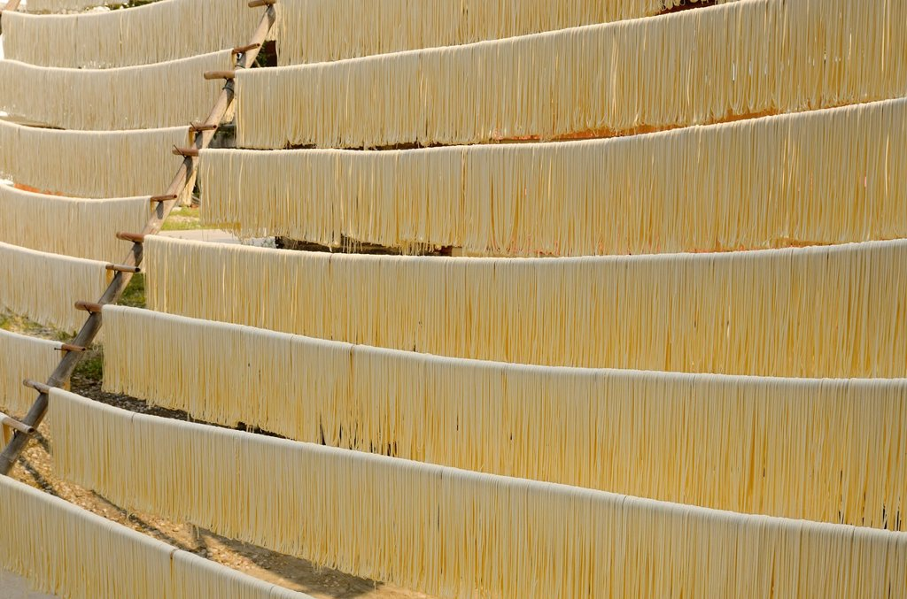Noodles hanging out to dry on rods in Fuli near Yangshuo China : Stock Photo