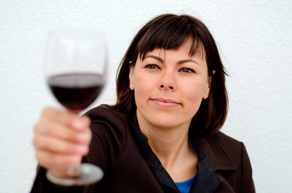 Woman holding up a glass of red wine : Stock Photo