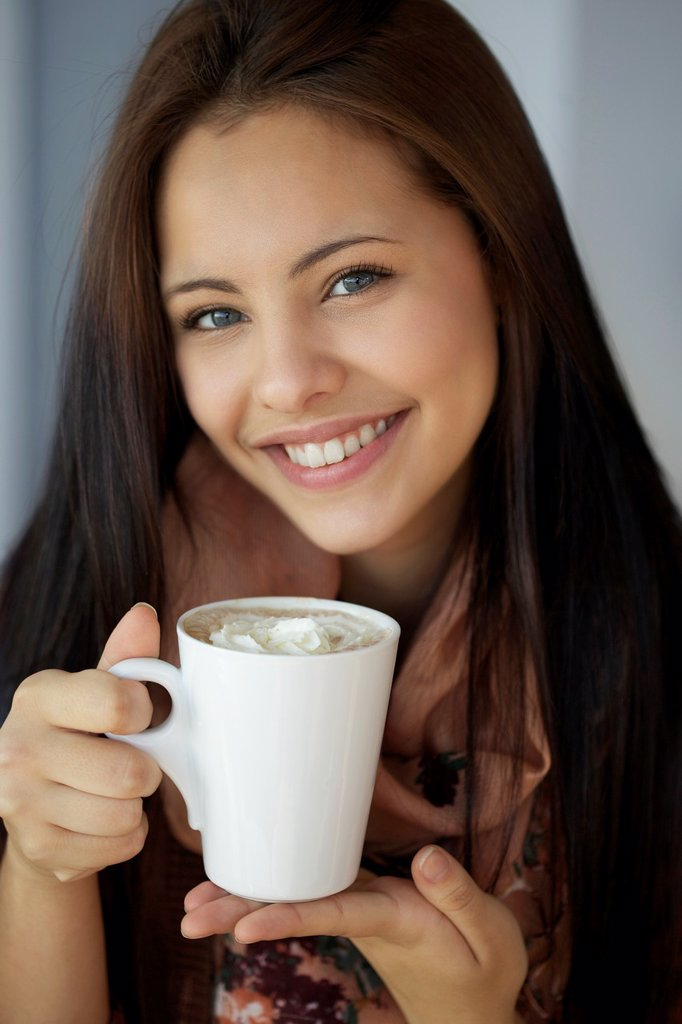 Stock Photo: 1436R-437143 Beautiful young girl holding hot chocolate and smiling in front of the camera