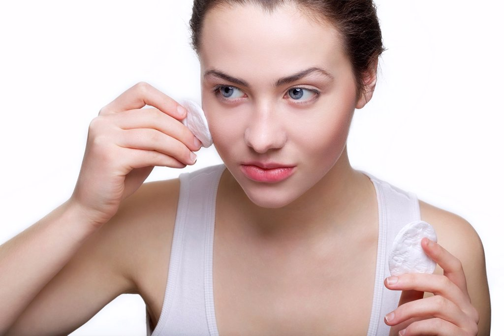 Stock Photo: 1436R-437160 Beautiful young woman removing make up with cotton swab pad