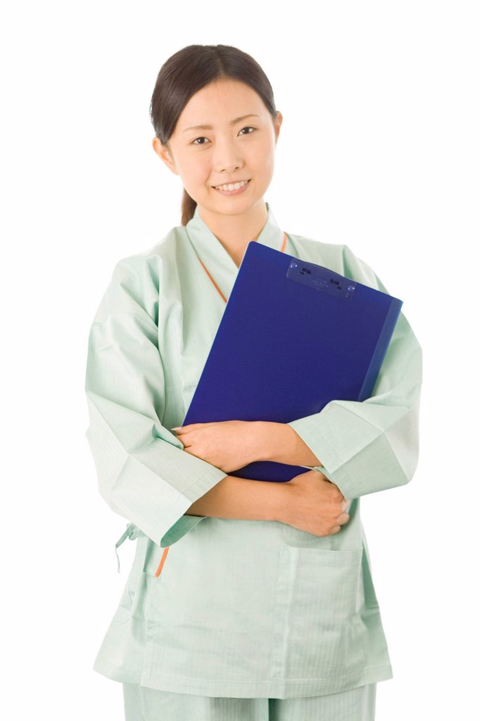 Stock Photo: 1436R-437279 Young woman in examination gown holding clip board
