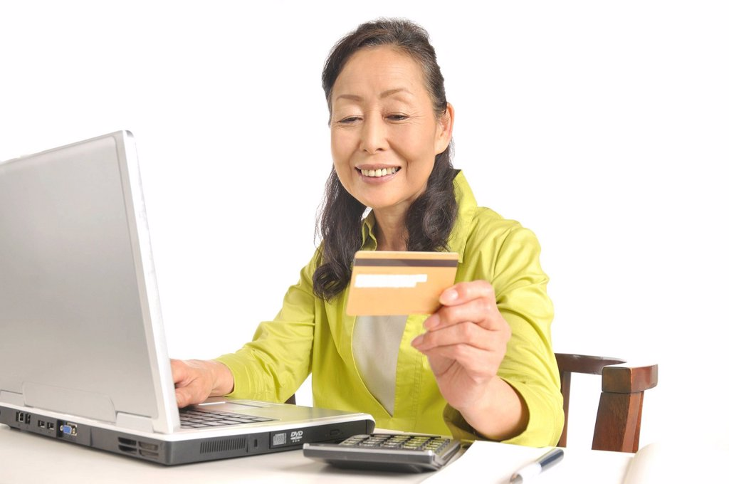 Senior woman holding credit card in front of laptop : Stock Photo