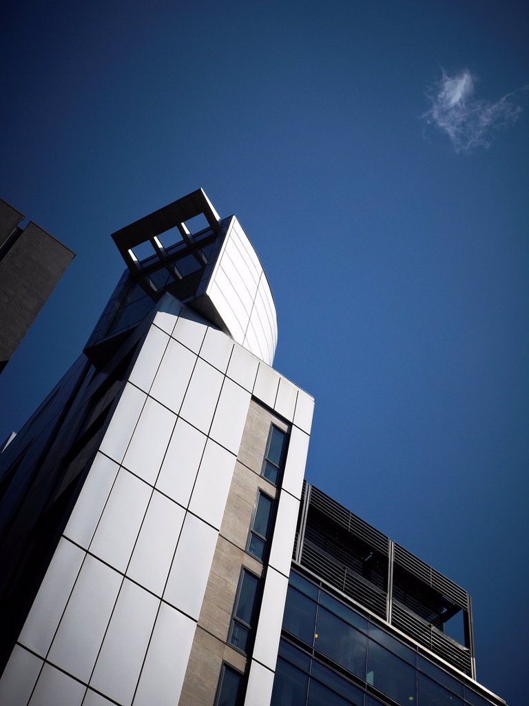 Stock Photo: 1436R-437950 Single cloud with detail of modern office building in the city centre of Manchester UK