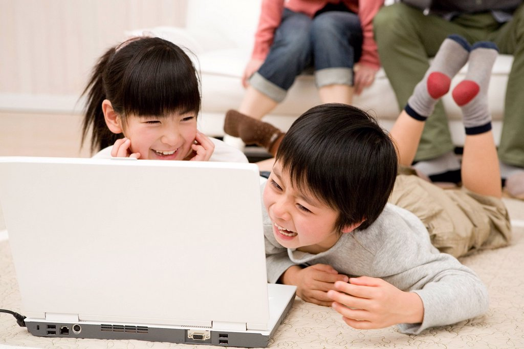 Two children looking laptop and laughing together : Stock Photo