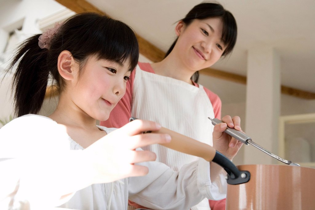 Stock Photo: 1436R-438587 Mother and daughter cooking together