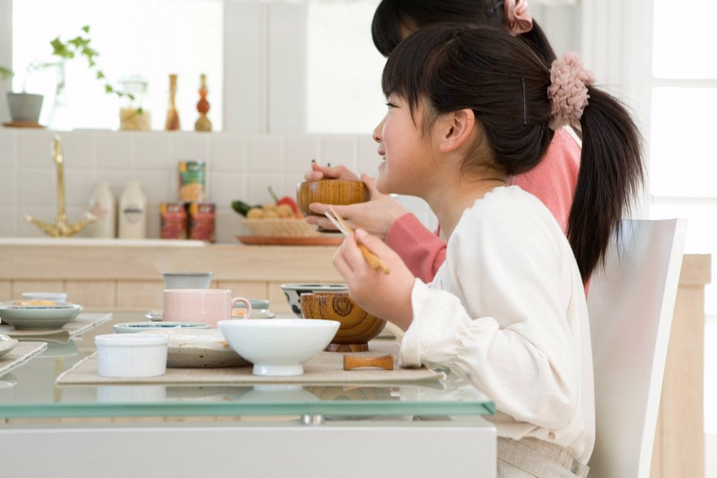 Daughter having meal with mother : Stock Photo