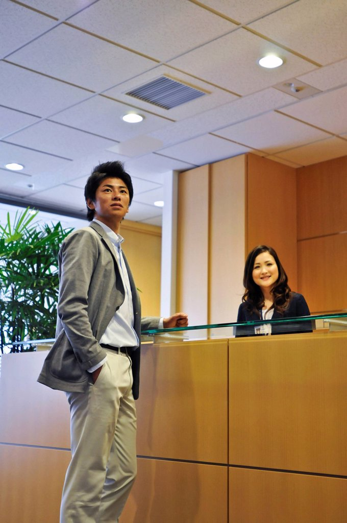 Stock Photo: 1436R-438648 Visitor and receptionist looking away at front desk