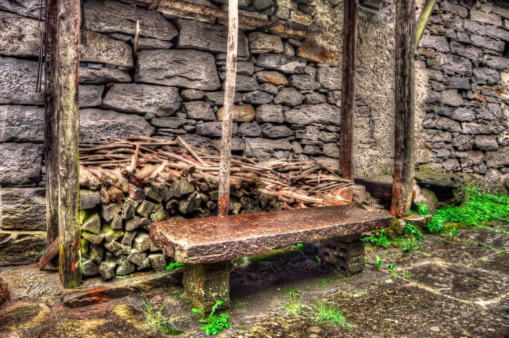 Stone bench and firewood close to a stone wall : Stock Photo