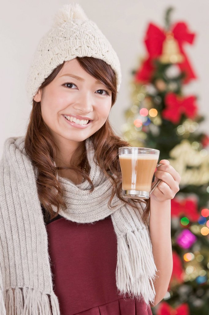 Stock Photo: 1436R-442436 Young Woman Holding Cappuccino Cup in front of Christmas Tree