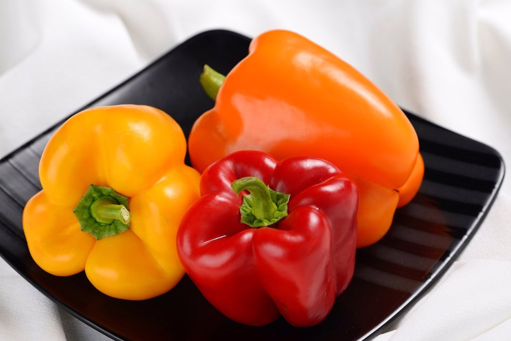 Stock Photo: 1436R-442873 Red yellow and orange bell peppers on a square black plate