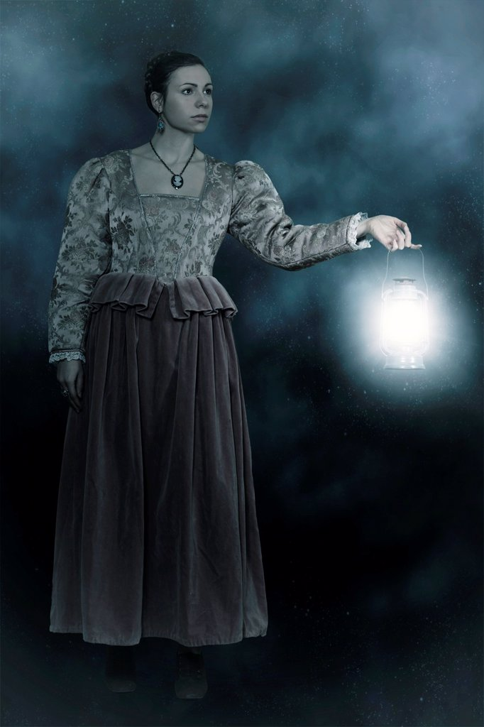 a woman in a victorian dress is holding a lantern in the dark : Stock Photo