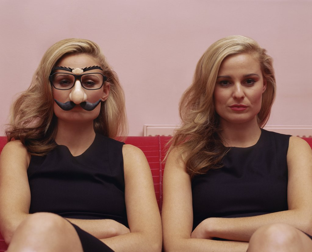 Stock Photo: 1439R-010795 Two women one wearing a comedy disguise