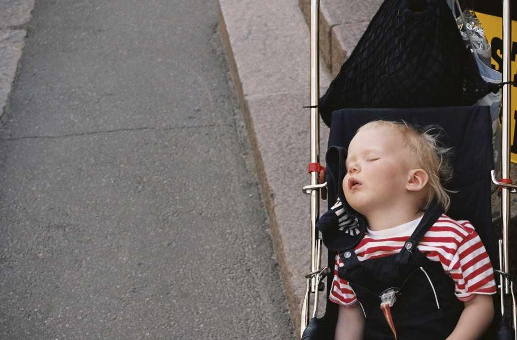 Baby asleep in a pushchair : Stock Photo