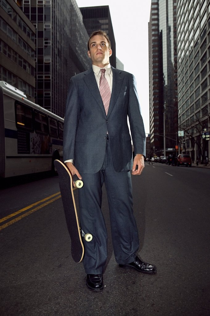 Businessman with a skateboard : Stock Photo