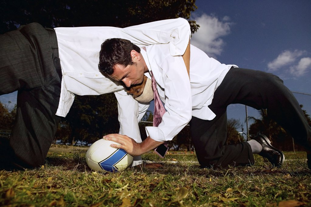 Businessmen playing rugby : Stock Photo