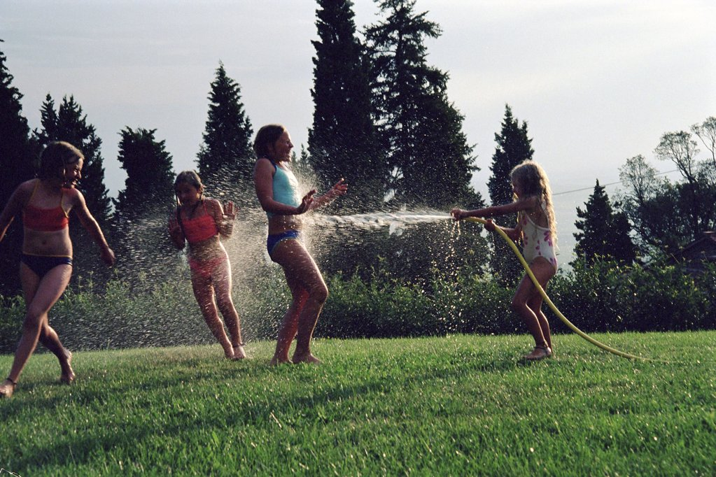 Girls playing with a hosepipe : Stock Photo
