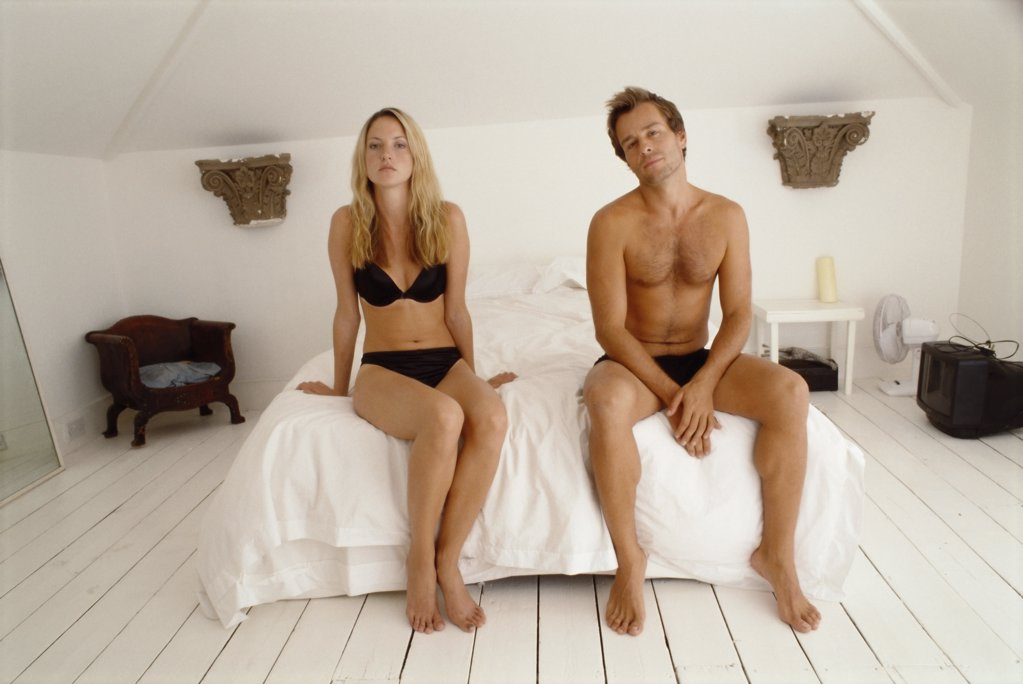 Stock Photo: 1439R-03776 Couple sitting on bed looking at camera
