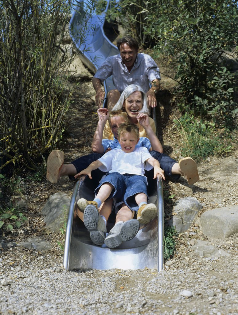 Family enjoy going on a slide. : Stock Photo