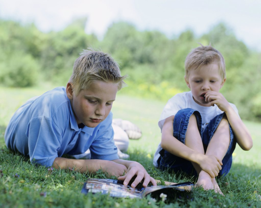 Stock Photo: 1439R-04005 Two boys relaxing outdoors.