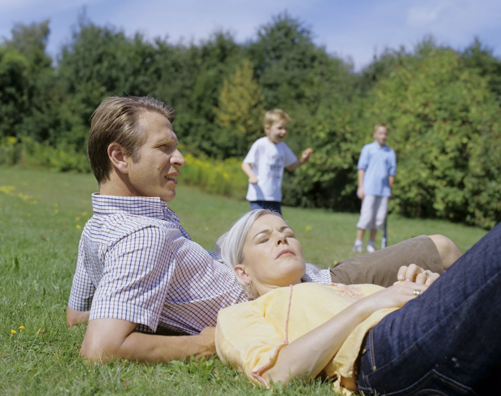 Stock Photo: 1439R-04009 Parents relax while boys play.
