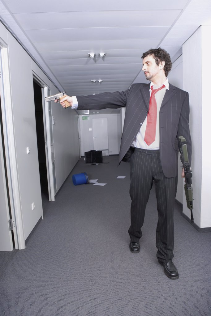 Stock Photo: 1439R-04234 Businessman using a handgun