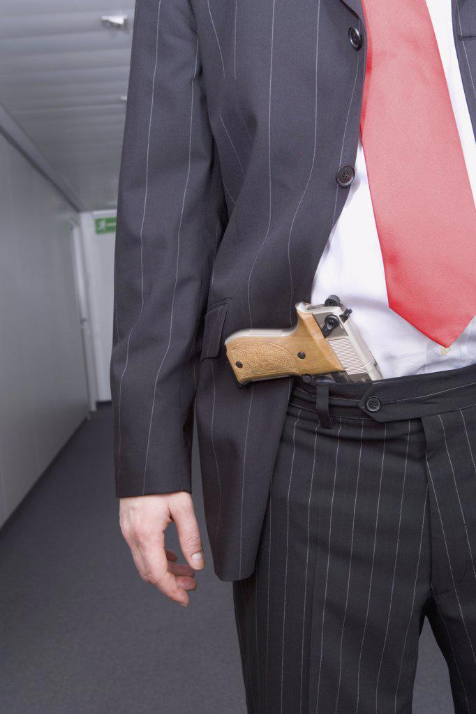 Businessman with a handgun : Stock Photo