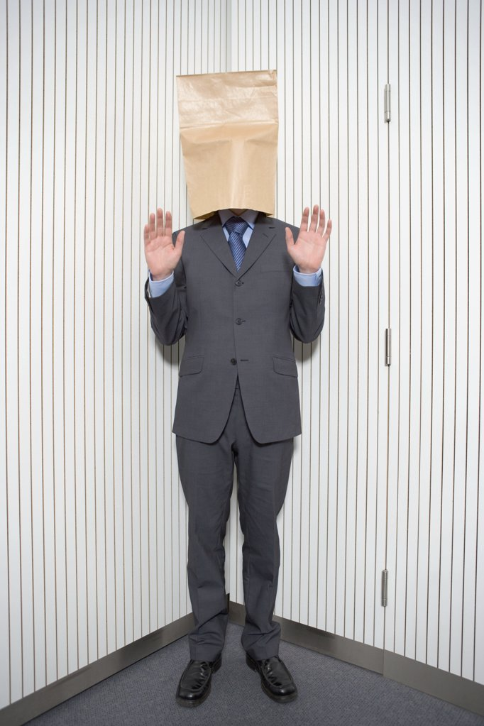 Stock Photo: 1439R-04242 Businessman with paper bag on head