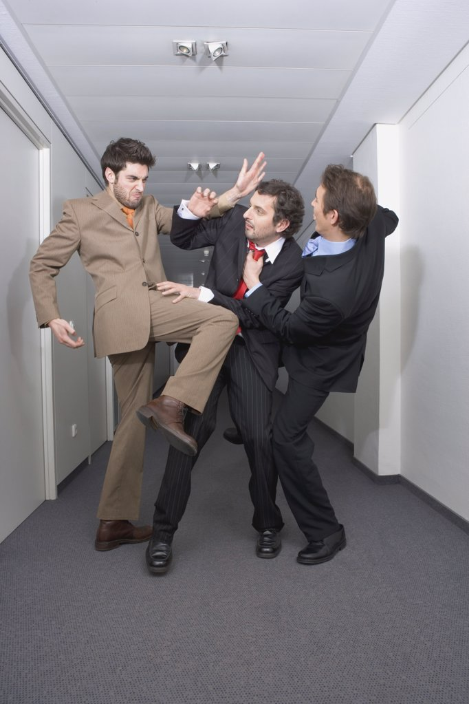 Businessmen fighting in corridor : Stock Photo