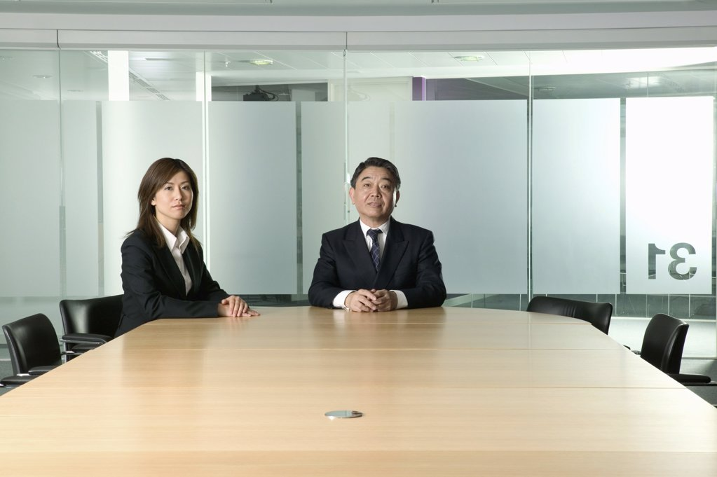 Stock Photo: 1439R-04267 Businessman and woman in conference room