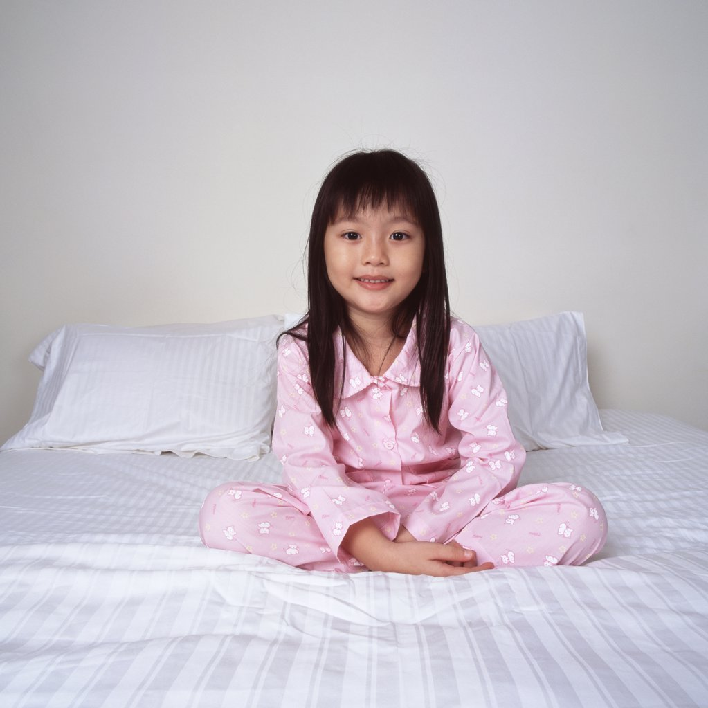 Smiling young girl on bed : Stock Photo