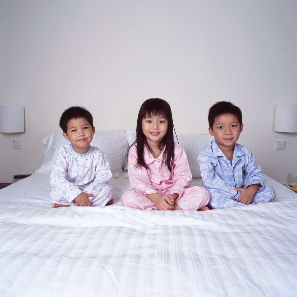Children on bed smiling : Stock Photo