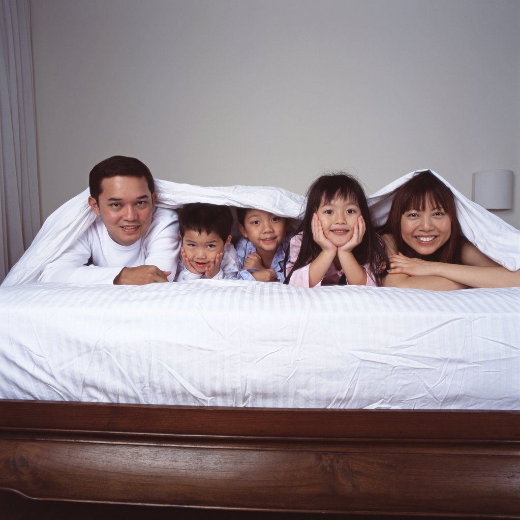 Happy young family in bed : Stock Photo