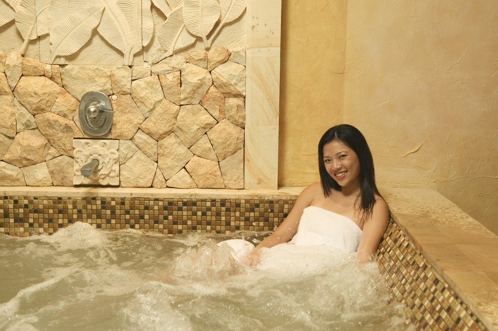 Stock Photo: 1439R-05237 Smiling woman in hot tub