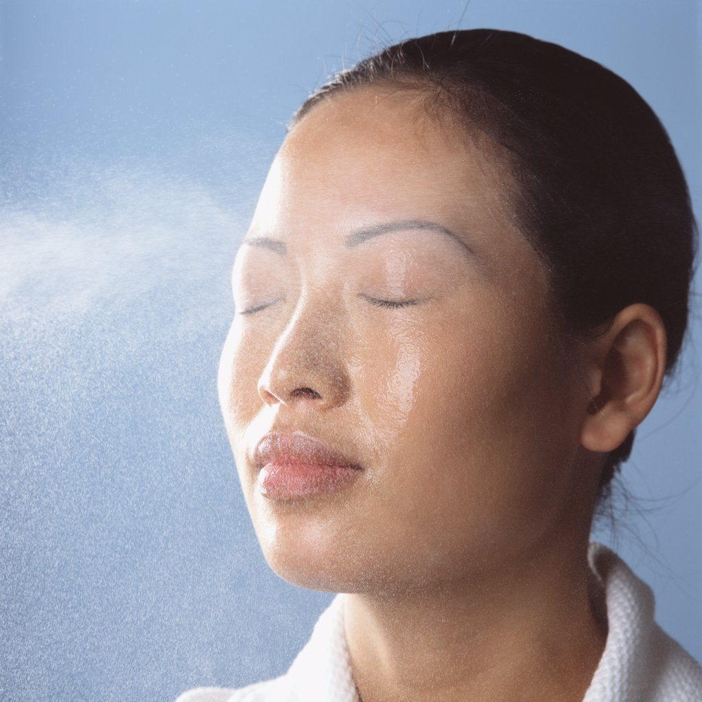 Water spraying on womans face : Stock Photo