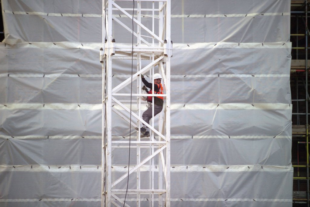 Worker on crane at site : Stock Photo