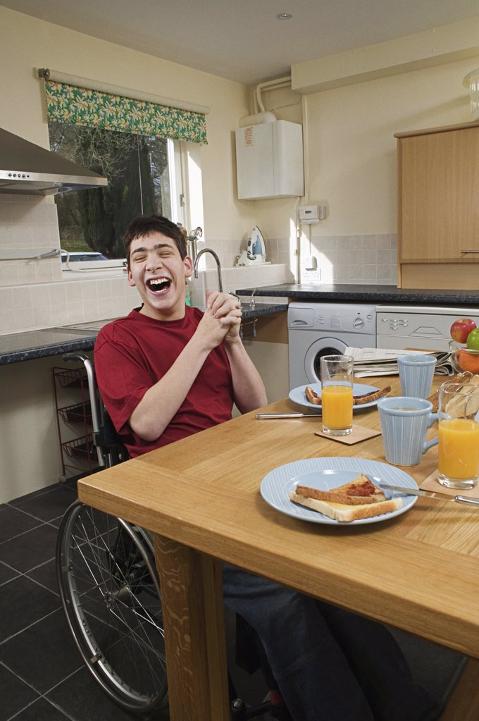 Disabled man laughing at breakfast table : Stock Photo