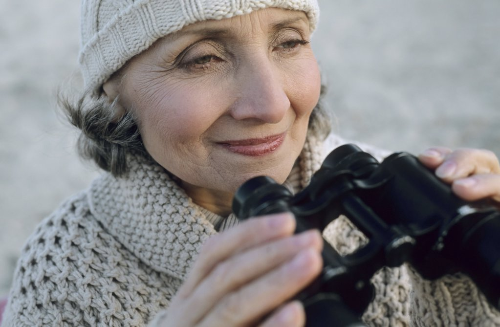 Stock Photo: 1439R-07393 Senior woman using binoculars