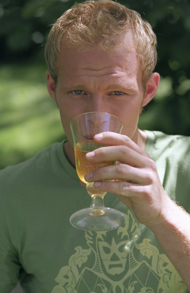 Young male drinking from glass : Stock Photo