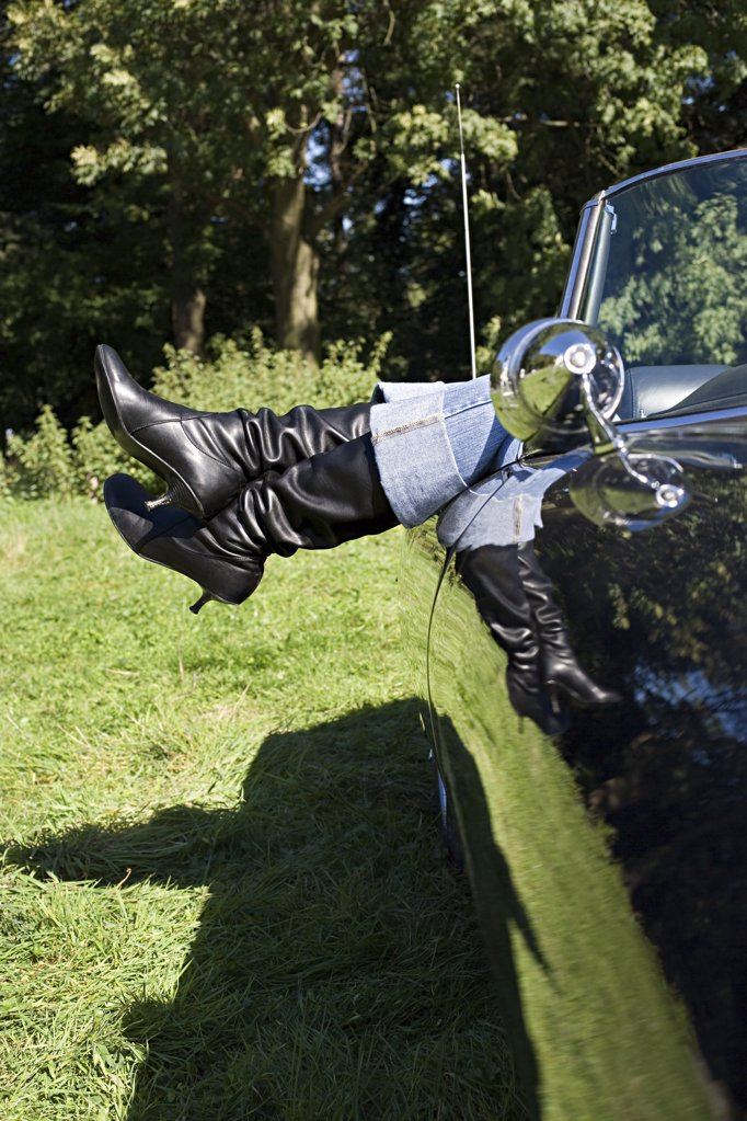 Stock Photo: 1439R-1000167 Womans feet sticking out of convertible
