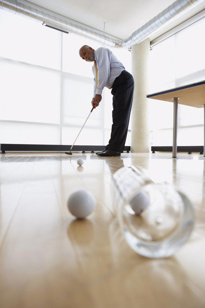 Businessman practicing putting : Stock Photo