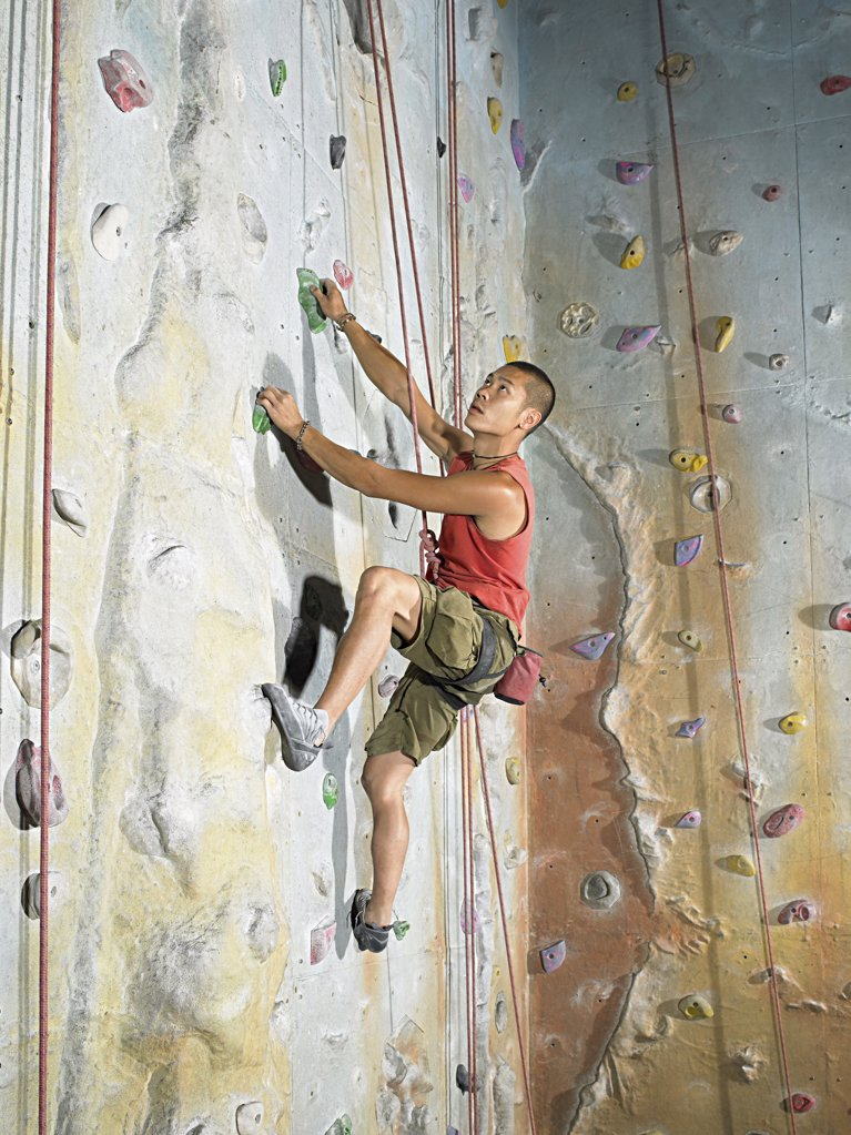 Stock Photo: 1439R-1003116 Man on climbing wall