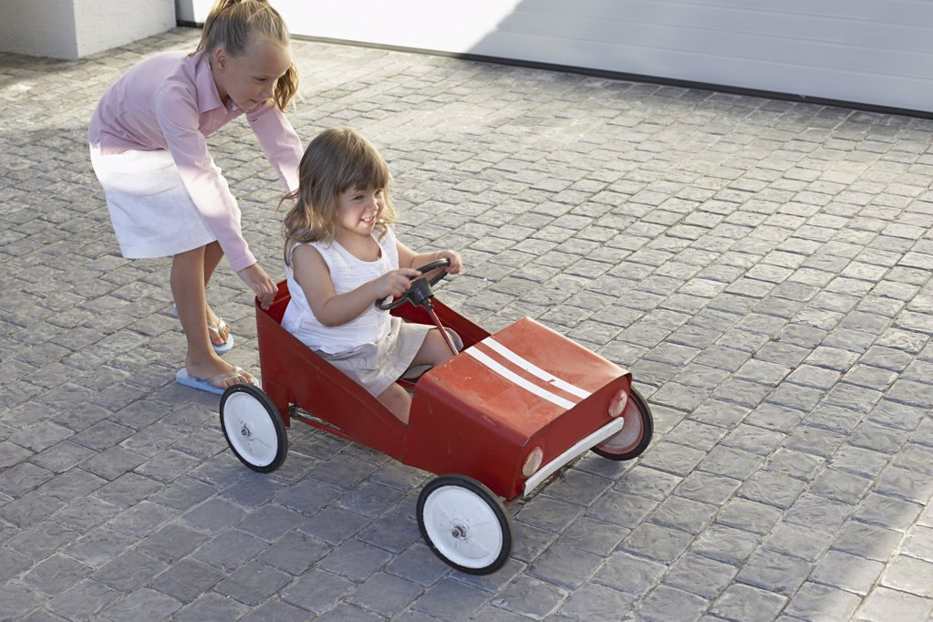 Sister pushing her younger sister in a toy car : Stock Photo