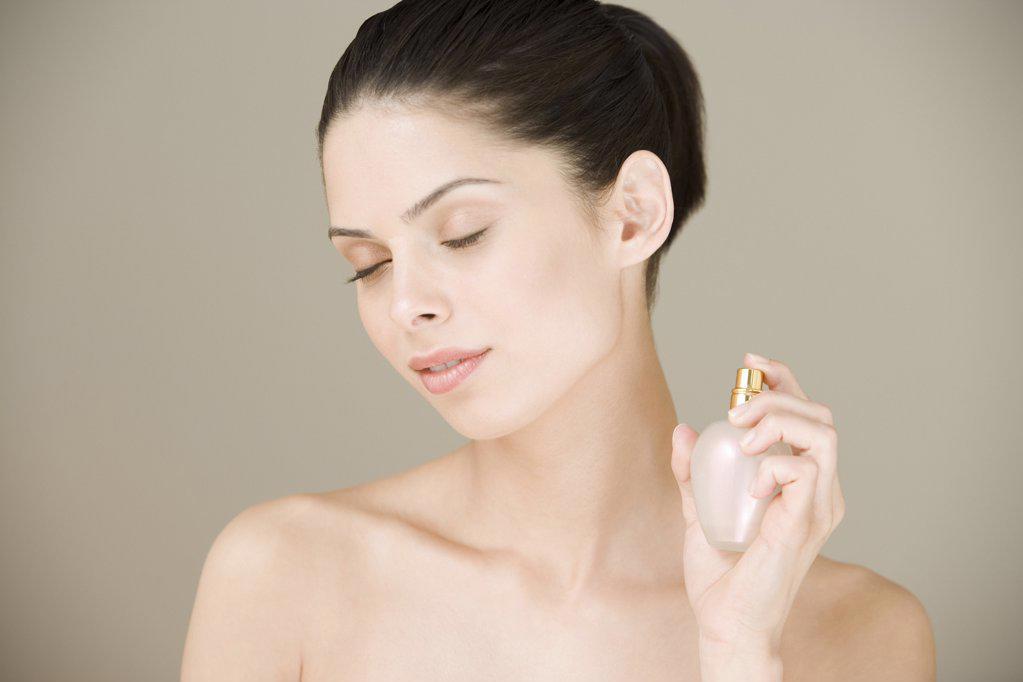 Young woman spraying perfume : Stock Photo