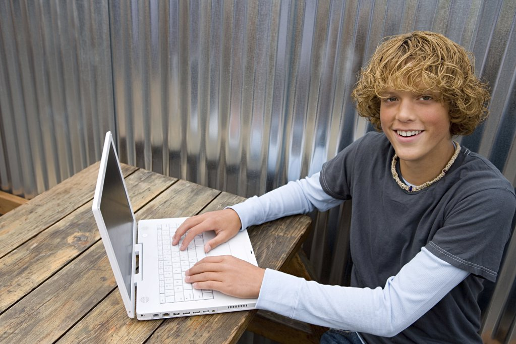 Stock Photo: 1439R-1004257 Teenage boy working on laptop