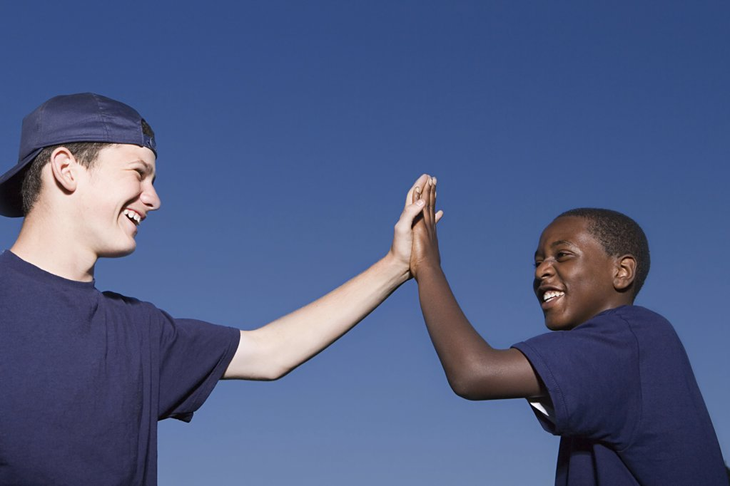 Two teenage boys giving a high five : Stock Photo