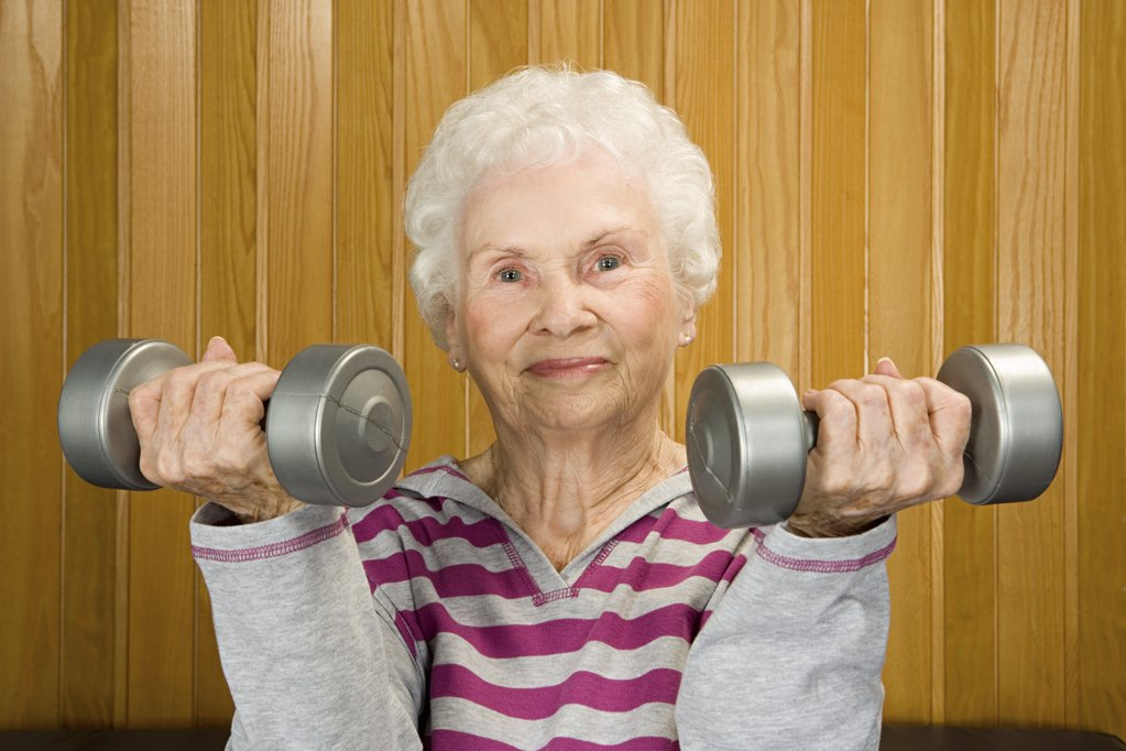 Senior woman lifting dumbbells : Stock Photo