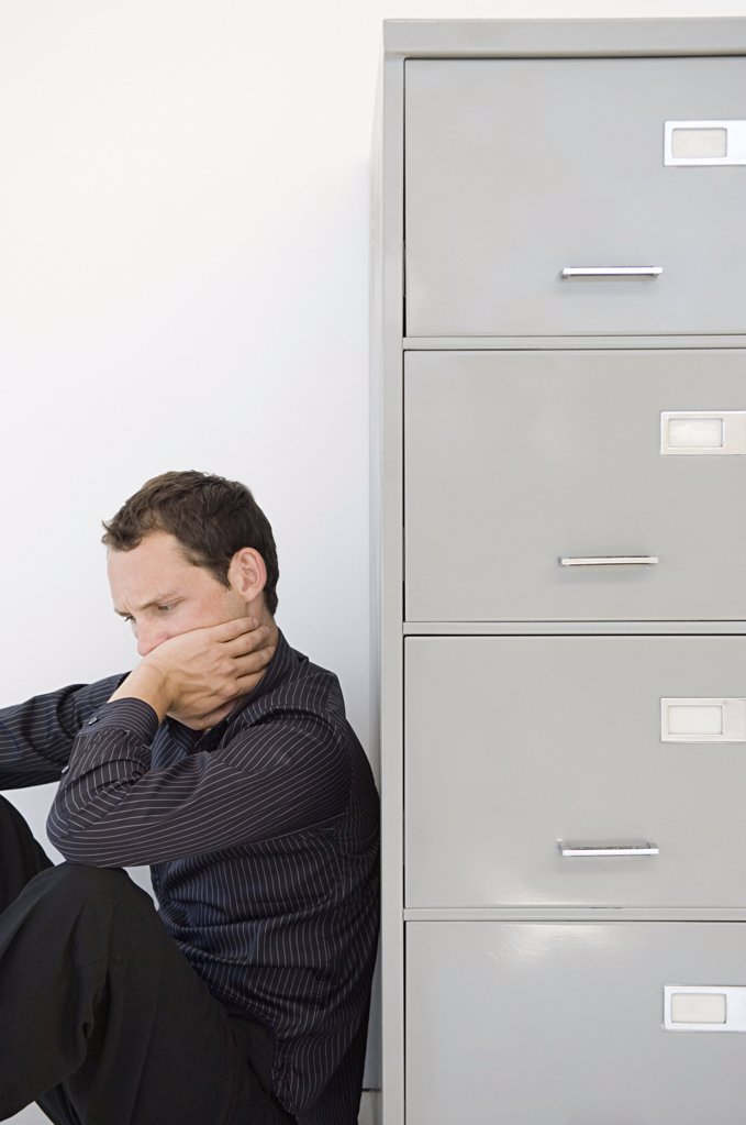 Businessman hiding behind filing cabinet : Stock Photo